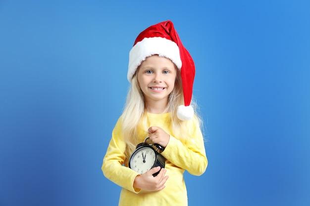 Jolie petite fille en bonnet de noel avec horloge. notion de compte à rebours de noël