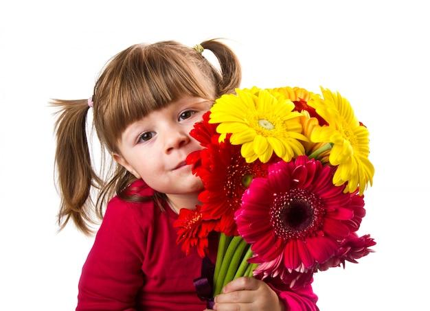 Jolie petite fille avec bouquet de fleurs de gerbera
