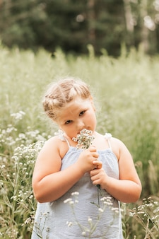 Jolie petite fille avec un bouquet de marguerites dans la nature en été