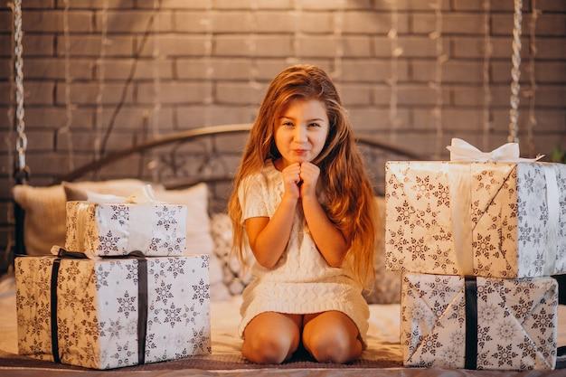 Jolie petite fille avec des cadeaux de noël au lit