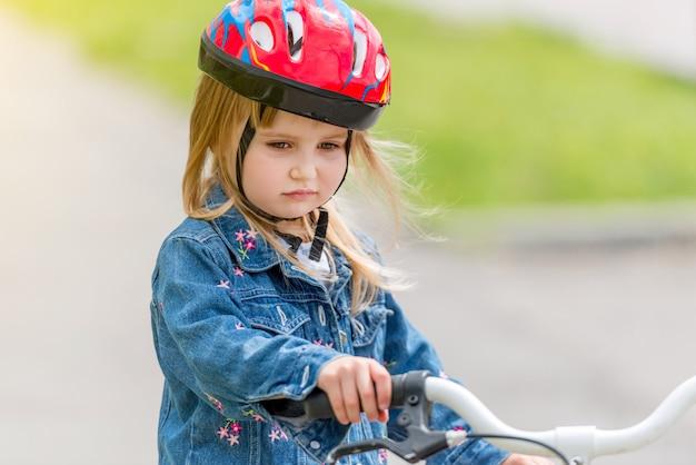 Jolie petite fille en casque et veste en jean sur un vélo