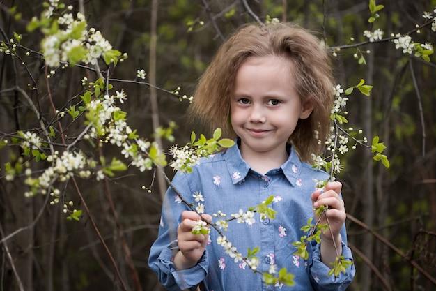 Jolie petite fille caucasienne de 5 ans dans un parc debout sous un cerisier en fleurs