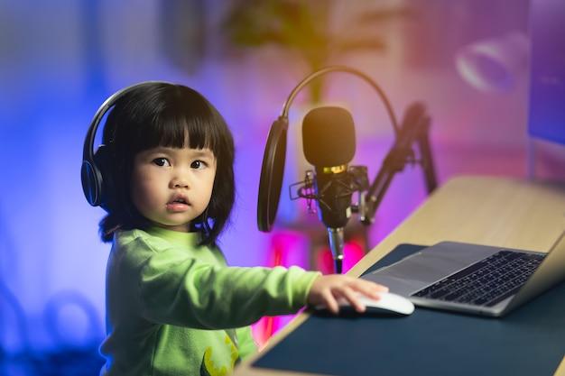 Jolie petite fille chantant avec un casque enregistrant une nouvelle chanson avec un microphone dans le studio d'enregistrement à domicile