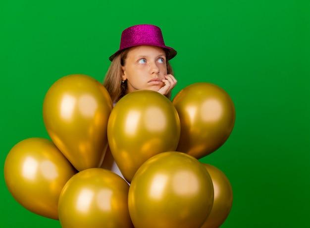 Jolie petite fille en chapeau de vacances avec bouquet de ballons à côté perplexe, concept de fête d'anniversaire debout sur fond vert