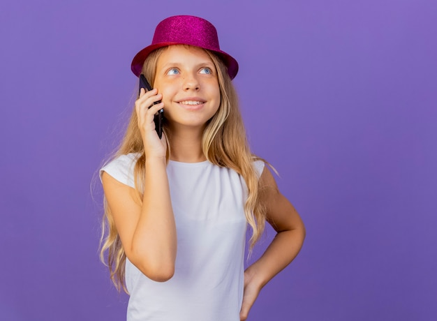 Jolie petite fille en chapeau de vacances parler au téléphone mobile souriant, concept de fête d'anniversaire debout sur fond violet