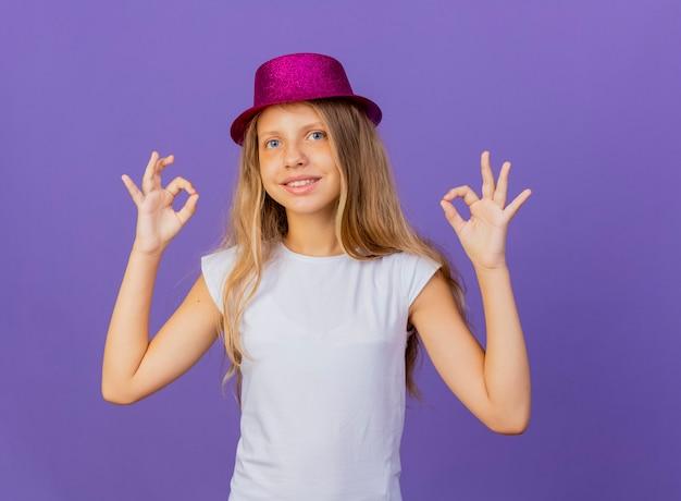Jolie petite fille en chapeau de vacances regardant la caméra en souriant avec un visage heureux montrant ok chanter, concept de fête d'anniversaire debout sur fond violet