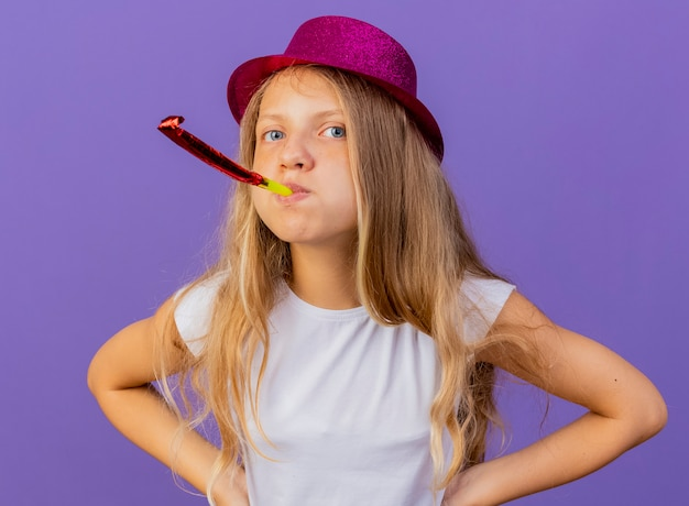 Jolie petite fille en chapeau de vacances soufflant sifflet d'être mécontent