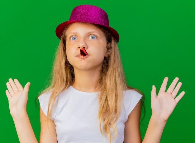 Jolie petite fille en chapeau de vacances soufflant sifflet