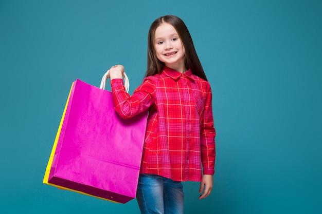Jolie petite fille en chemise à carreaux aux cheveux bruns tient des sacs différents