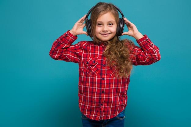 Jolie petite fille en chemise à carreaux et écouteurs aux cheveux bruns