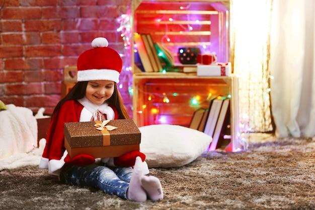 Jolie petite fille en costume de carnaval assis dans la salle décorée de noël