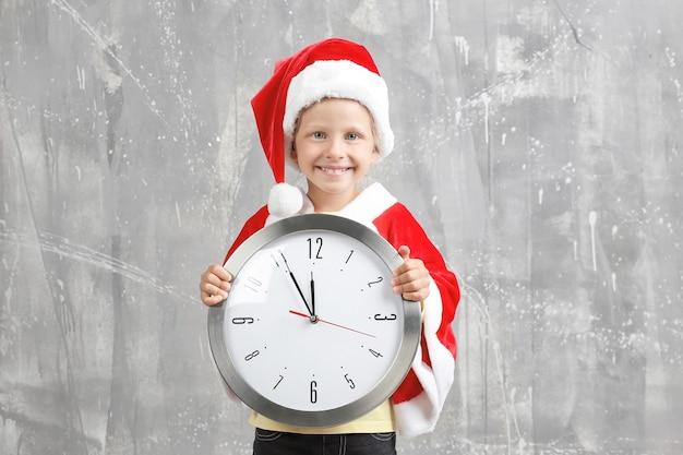 Jolie petite fille en costume de père noël avec horloge sur surface grunge