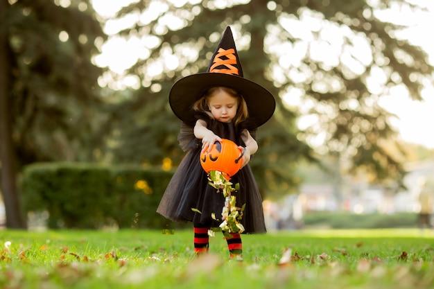 Une jolie petite fille en costume de sorcière se promène dans la rue avec un bonbon en forme de citrouille.