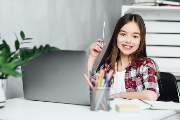 Jolie petite fille avec un crayon à portée de main à l'aide d'un cahier tout en préparant les devoirs