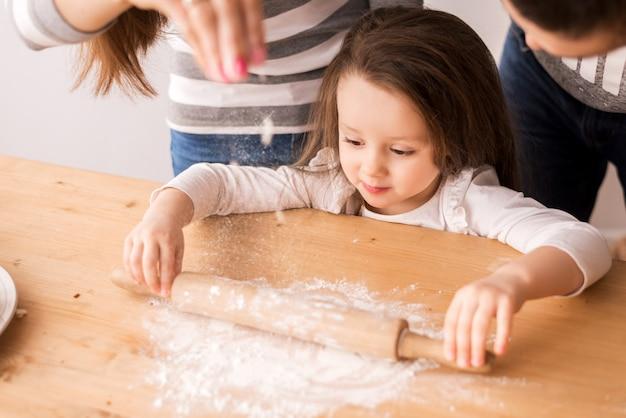 Jolie petite fille cuisine dans la cuisine. roule la pâte avec de la farine sur les biscuits et les petits pains