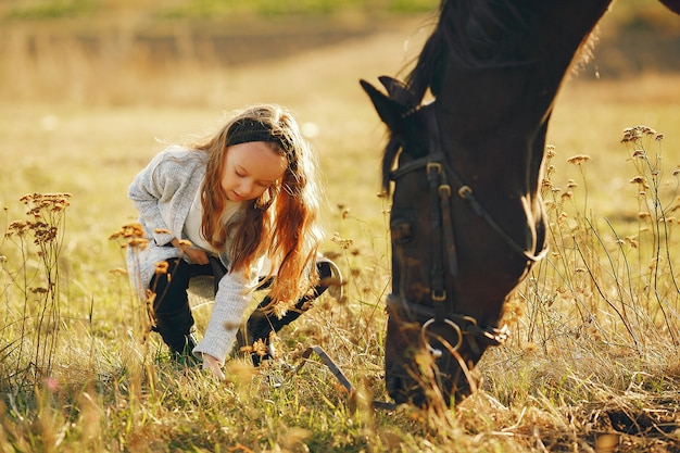 Jolie petite fille dans un champ d'automne avec cheval