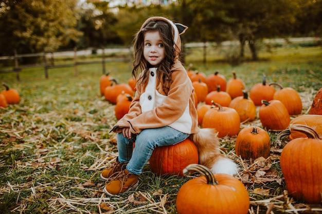 Jolie petite fille dans le champ de la citrouille
