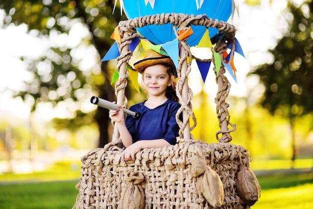 Une jolie petite fille dans un chapeau de paille sourit dans un panier de ballon. enfance, aventure