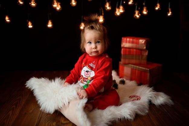 Jolie petite fille dans un costume de noël rouge avec des guirlandes rétro est assis sur une fourrure
