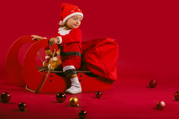 Une jolie petite fille dans un costume de père noël rouge, sur un traîneau accompagné de rennes avec des cadeaux et des décorations d'hiver.
