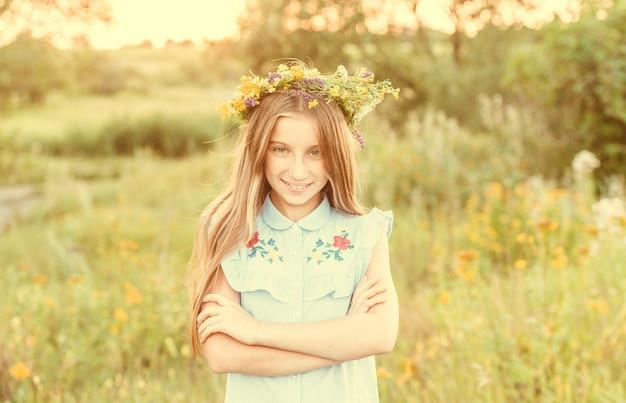 Jolie petite fille dans une couronne de fleurs