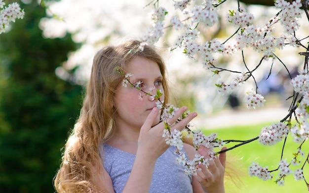 Jolie petite fille dans le jardin de pommiers en fleurs sur une belle journée de printemps