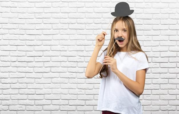 Jolie petite fille dans un papier avec des accessoires photo drôles. enfant heureux