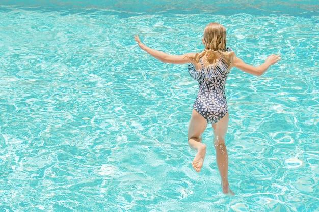Jolie petite fille dans la piscine, vacances d'été.
