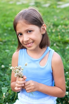 Une jolie petite fille dans un pré un jour d'été sourit et regarde la caméra, tenant un bouquet de fleurs d'été dans ses mains.