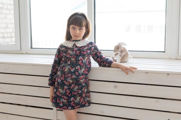 Jolie petite fille dans une robe à fleurs avec un lapin doux jouet préféré. le concept des enfants