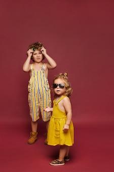 Jolie petite fille dans une robe et des lunettes de soleil et petit garçon dans une salopette élégante d'été et des lunettes de soleil, isolé en pleine longueur sur le fond rose