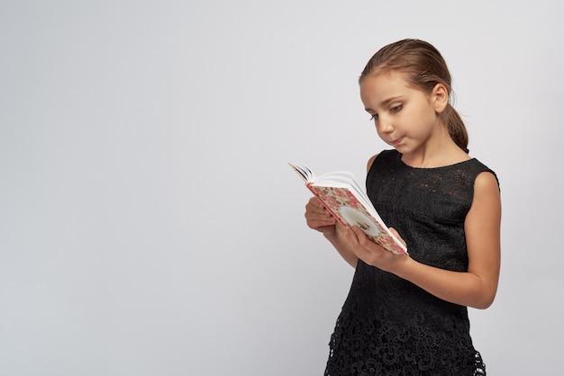 Jolie petite fille dans une robe noire avec une expression pensive passionnée en lisant un livre. portrait en studio grand fond blanc isolé