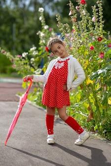 Une jolie petite fille dans une robe rouge et un chemisier blanc avec un parapluie de canne rose se dresse sur un été
