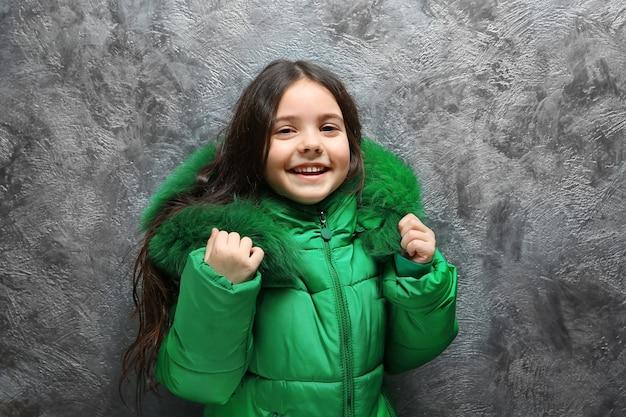 Jolie petite fille dans des vêtements chauds, debout près d'un mur texturé gris