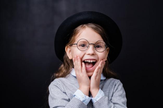 Jolie petite fille dans des vêtements décontractés intelligents et des lunettes exprimant la stupéfaction ou l'excitation en se tenant debout devant la caméra