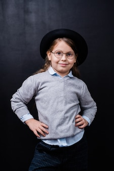 Jolie petite fille dans des vêtements décontractés et des lunettes debout devant la caméra contre l'espace noir