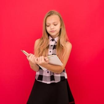Jolie petite fille debout et livre de lecture sur rouge -