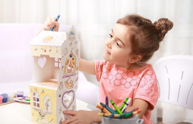Jolie petite fille dessin avec des crayons à la maison