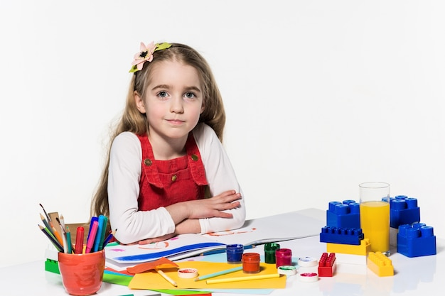 Jolie petite fille dessin avec de la peinture et un pinceau à la maison