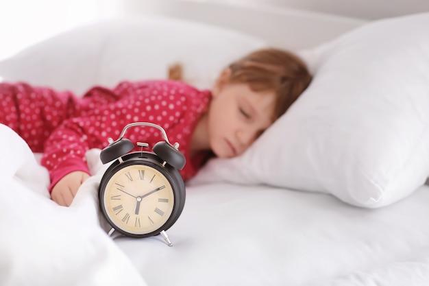 Jolie petite fille dormant dans son lit avec réveil
