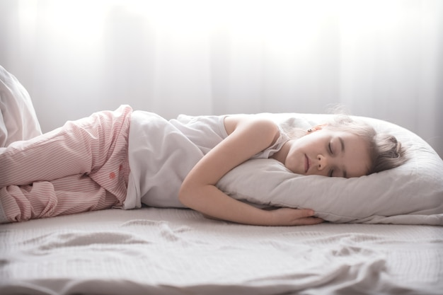 Jolie petite fille dort doucement dans un lit douillet blanc, le concept de repos et de sommeil des enfants