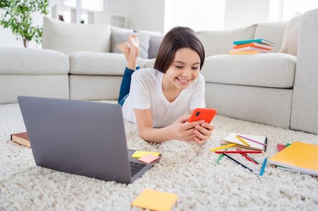 Jolie petite fille douce poser un tapis tenir un téléphone intelligent parcourir le réseau social