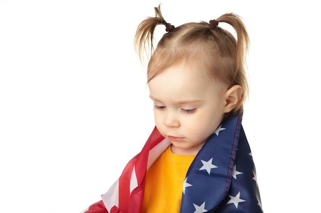 Jolie petite fille avec le drapeau américain isolé sur blanc.