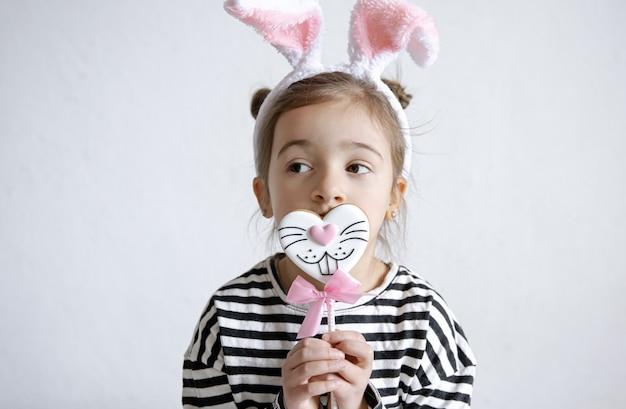 Jolie petite fille avec du pain d'épice de pâques sur un bâton et des oreilles de lapin décoratives sur sa tête