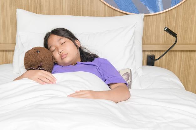 Jolie petite fille embrasse un ours en peluche tout en dormant dans son lit à la maison, le repos et le concept de soins de santé