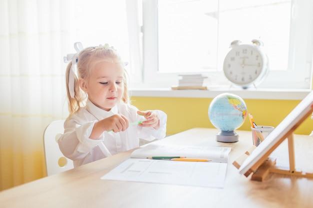 Jolie petite fille enfant d'âge préscolaire avec deux histoires de cheval en chemise blanche, dessinant à la maison à la table. retour au concept d'école.