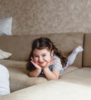 Une jolie petite fille est allongée sur le canapé sur le ventre avec ses mains sous sa tête. le concept du bonheur des enfants
