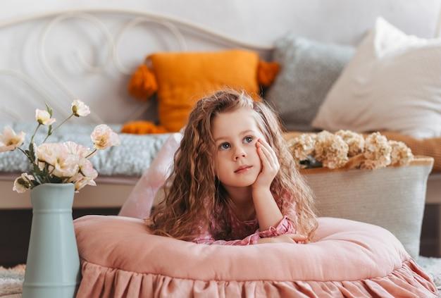 Une jolie petite fille est allongée sur le sol dans la chambre des enfants et rêve. intérieur vintage