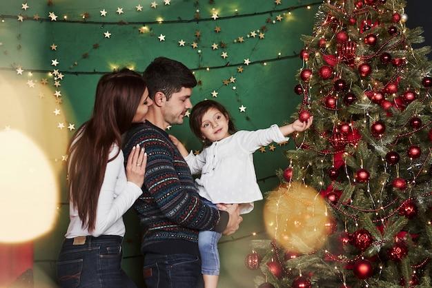 Jolie petite fille est en contact avec la sphère de vacances rouge. famille heureuse fête. nouvel an et debout près d'un arbre de noël