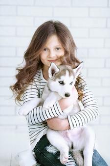 Jolie petite fille étreignant un chiot husky sur blanc